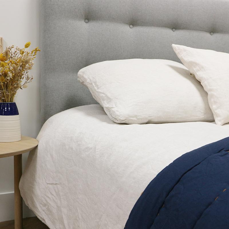 Tête de lit déco sur le lit avec ses oreillers et sa couette