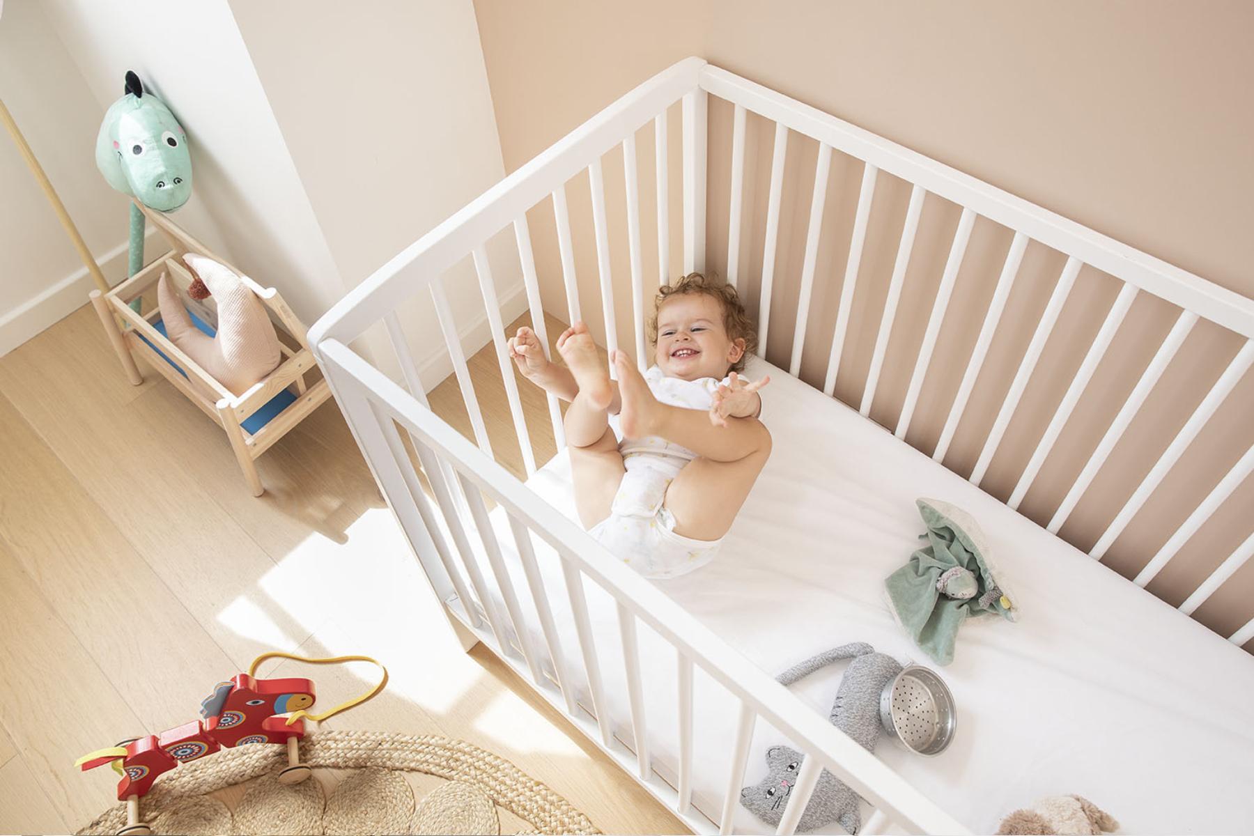 Bébé joue les pieds en l'air dans son lit à barreaux sur son matelas Bébé Ilobed.