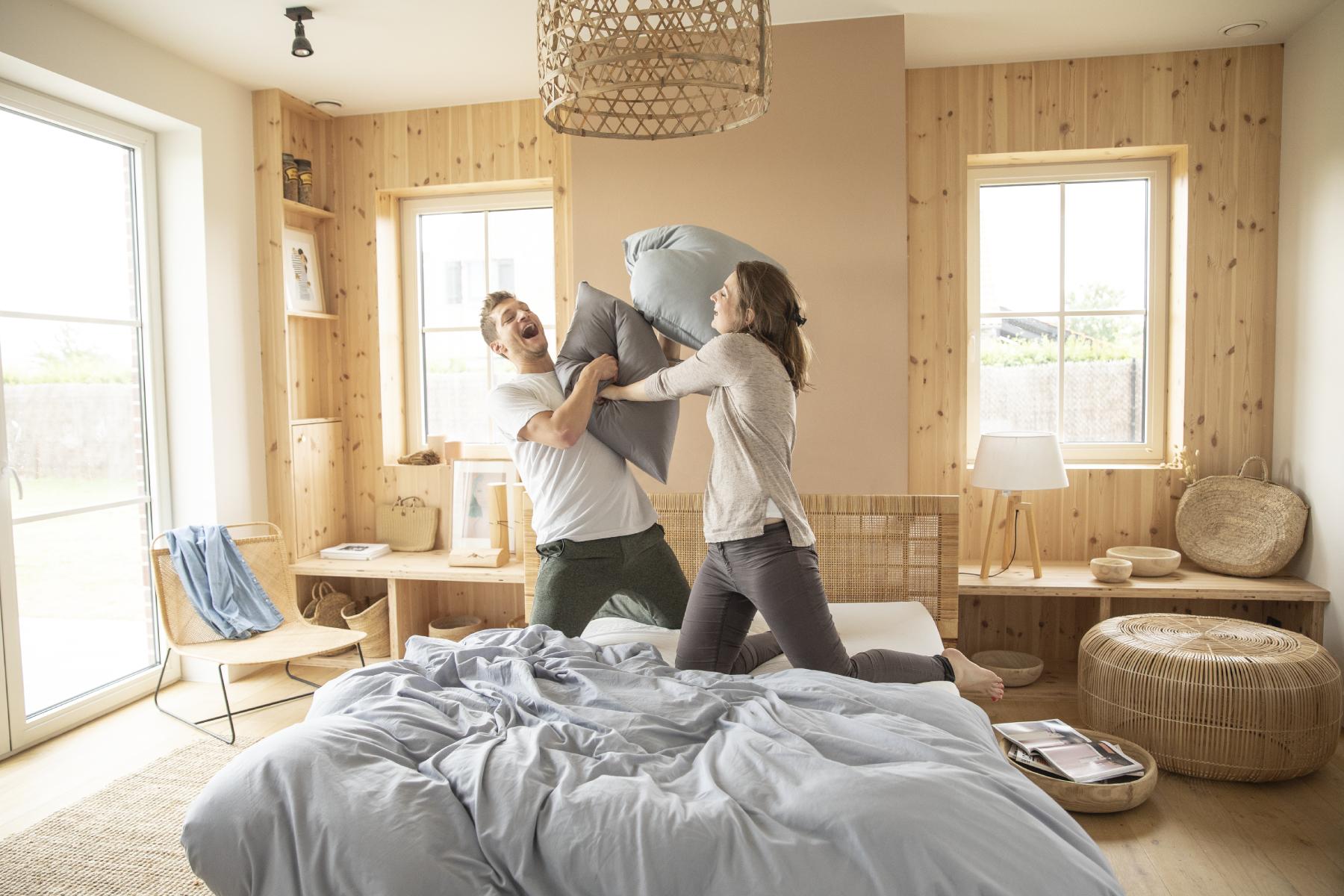 Le matelas Mousse Mémoire et le sommier à lattes Ilobed sont très confortables : un couple fait une bataille d'oreillers dessus dans une chambre cosy.