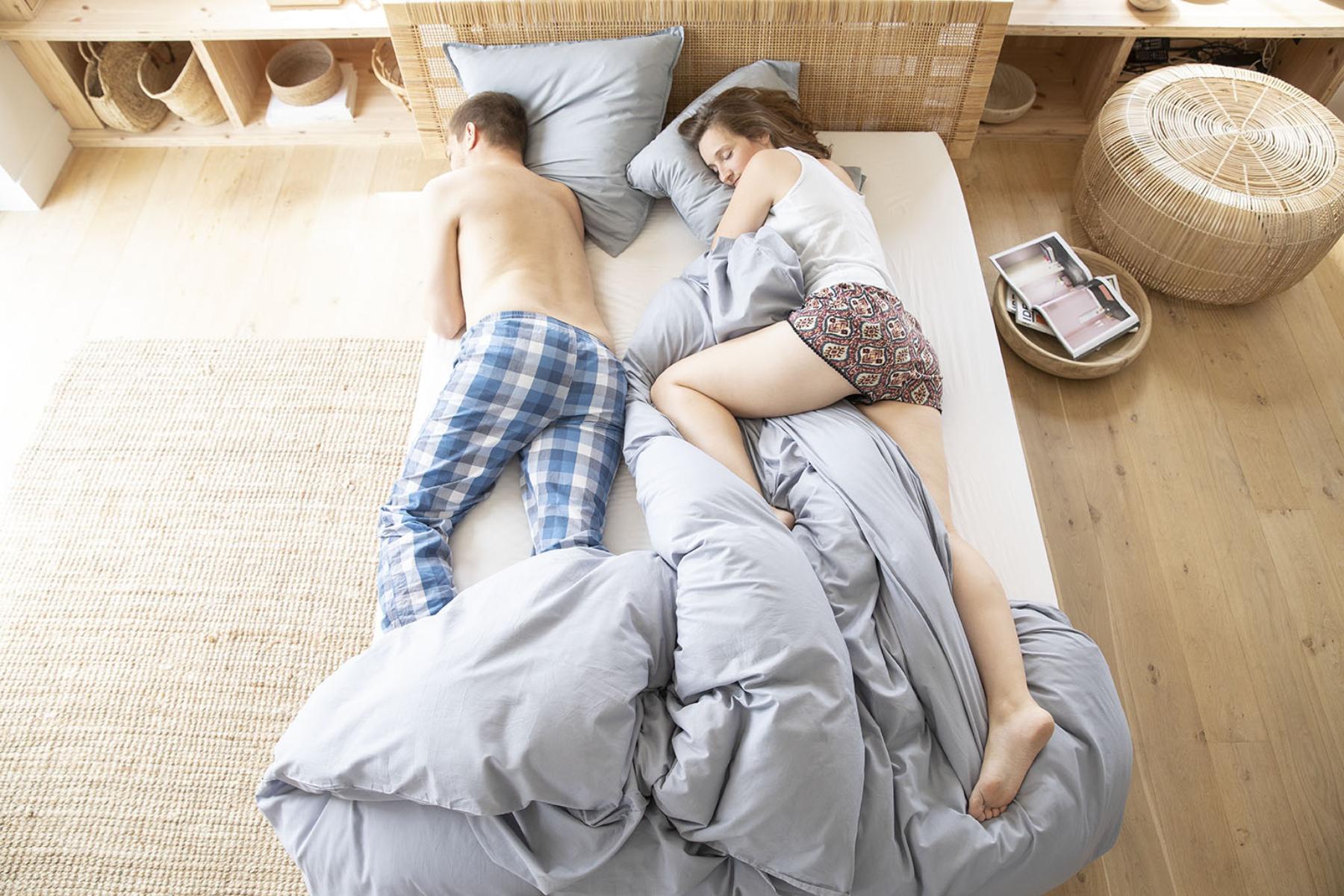 Un coupe dort enveloppé dans la couette sur le matelas Made in France Ilobed et son sommier tapissier.